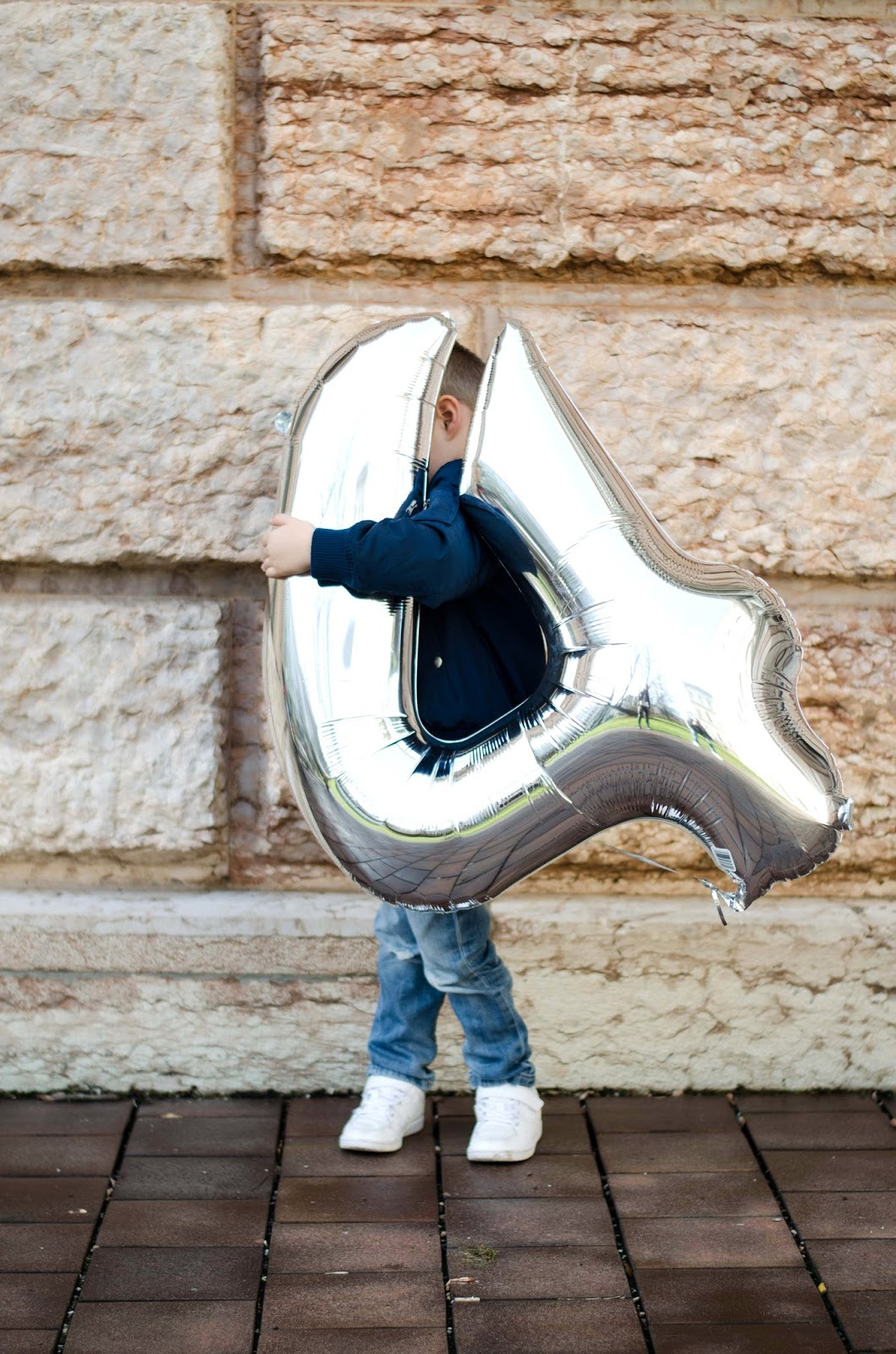 toddler with big silver number 4 balloon