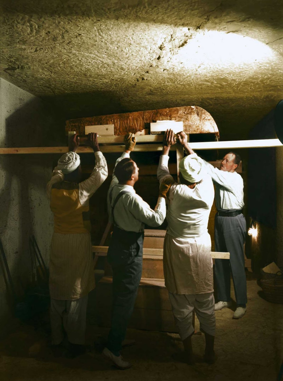 Carter, Callender and two Egyptian workers carefully dismantle one of the golden shrines within the burial chamber.