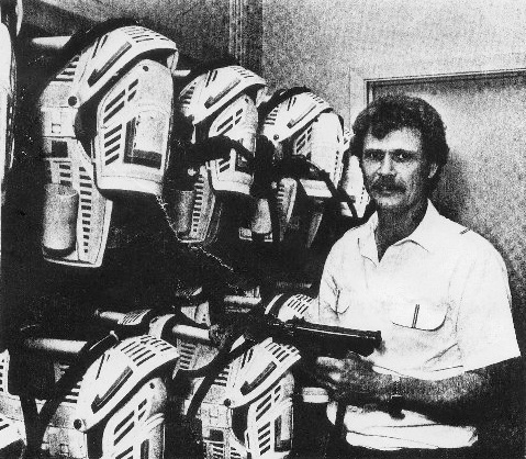 Bill Lewis in suit-up room holding one of the light guns