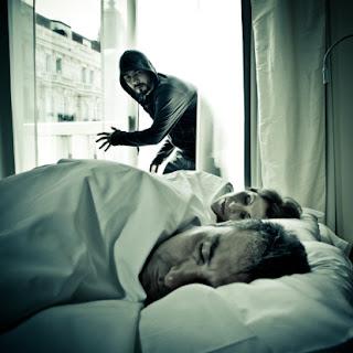 Encapuchado con barba y sudadera negra entra por la ventana de una casa con un hombre y una mujer dormidos en la cama.
