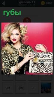 Женщина с сумкой цвета блузки и ярко накрашенные губы. Блондинка на фоне розового цвета