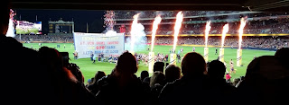 "View from level 1 of Adelaide Oval - the Adelaide Crows team run out onto the ground with a guard of honour and fireworks. The banner through which the team will run reads ""Friday night footy at our home ground, our 600th game, let's make it loud"""