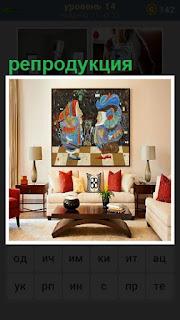 в комнате на стене висит картина, репродукция и стоит диван рядом
