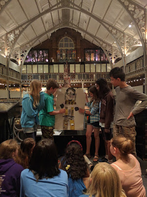 Children stand in the Pitt Rivers Museum and hold up their costume design