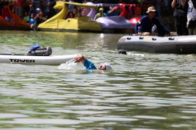 Wakil Gubernur DKI Jakarta Sandiaga Uno berenang saat adu cepat melawan Menteri Kelautan dan Perikanan Susi Pudjiastuti di Danau Sunter, Jakarta Utara