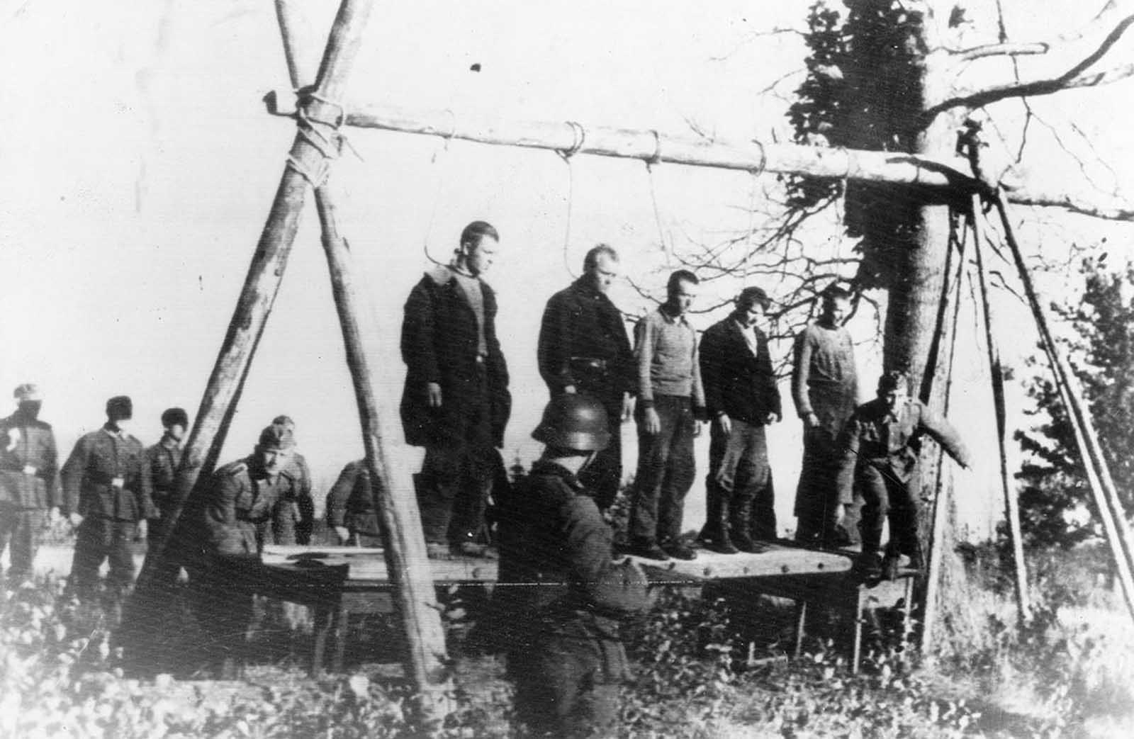 Five Soviet civilians on a platform, with nooses around their necks, about to be hanged by German soldiers, near the town of Velizh in the Smolensk region, in September of 1941.
