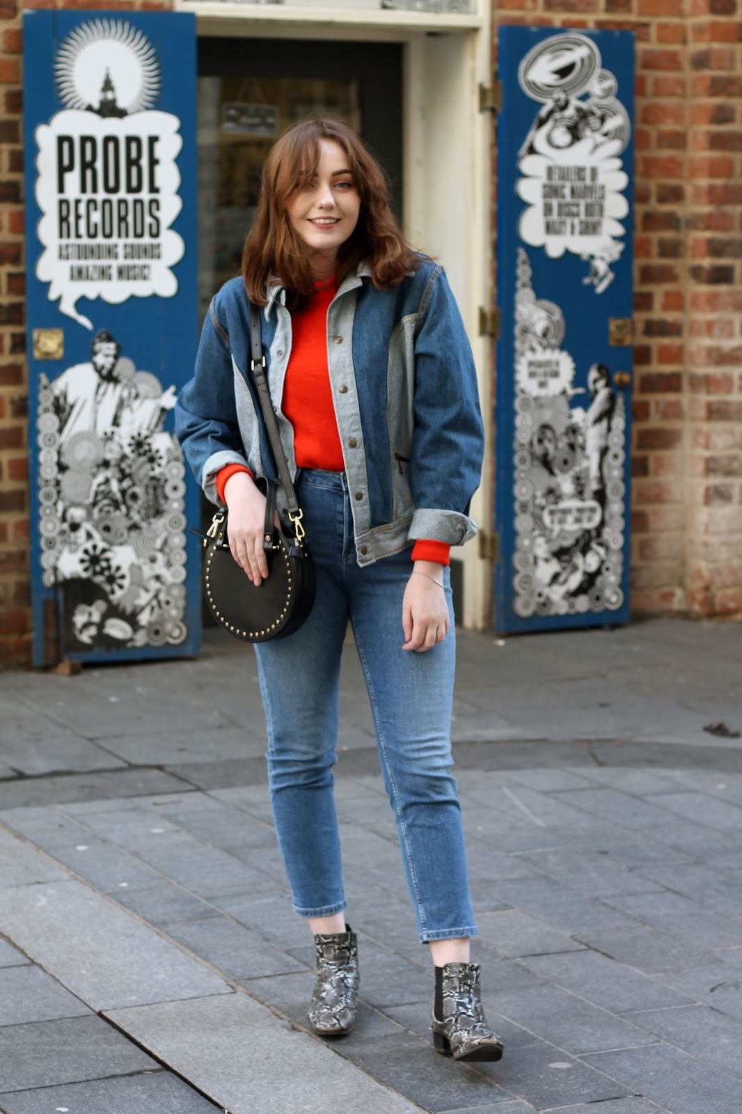 double denim with jacket and blue jeans paired with orange turtleneck jumper, black studded cross body bag and snake print ankle boots for western ss18 trend