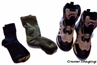 Photograph of cold weather foot gear namely black sock liners, green heavy duty socks, and khaki and black snow boots by Cramer Imaging