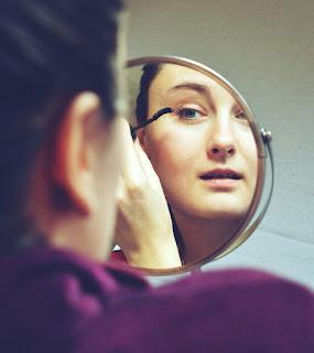 Mulher com os cabelos presos maquia-se em frente a um espelho de bancada redondo.