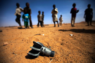 Children stare at the remnant of a mortar projectile recently abandoned in the Alabassi camp for Internally Displaced People, in Mellit, North Darfur