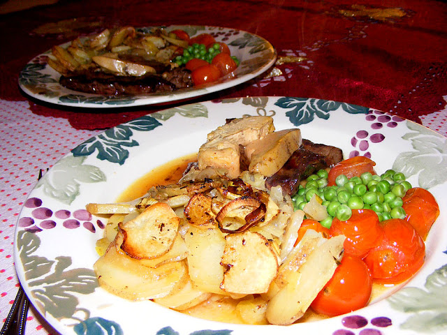 Flashed beef flank steak topped with foie gras served with roasted cherry tomatoes, peas and pommes boulangere. Cooked and photographed by Susan from Loire Valley Time Travel. https://tourtheloire.com