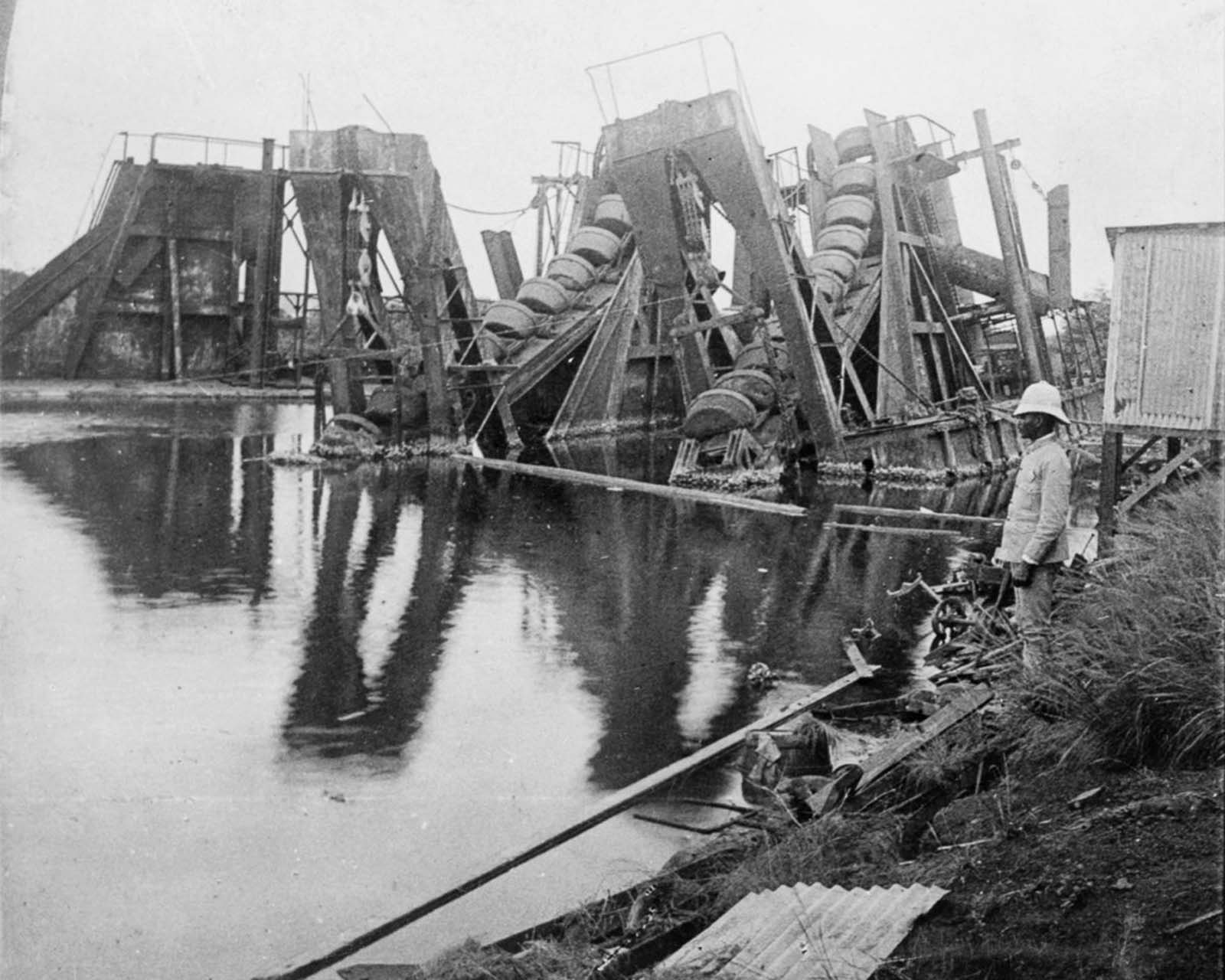 A man stands near dredging equipment abandoned by the French. 1906.