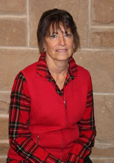 Woman with brown hair wearing a red plaid shirt and solid red vest stands in front of a stone wall