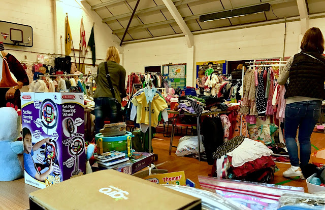 A view from the corner of the scout hall looking out towards lots of tables piled high with second hand children's clothes and toys