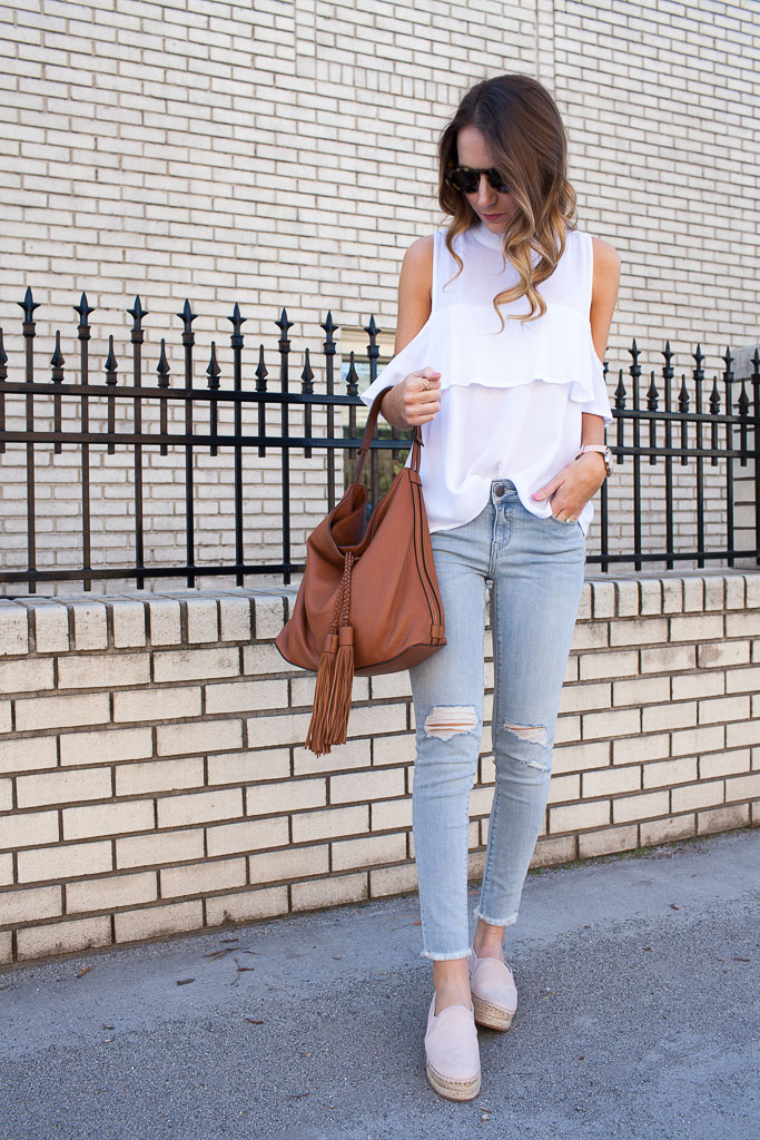 A cold shoulder ruffle top with distressed denim and espadrilles.