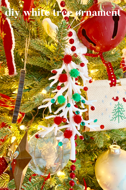 White tree ornament decorated with red and green sequins and pompoms hanging from a decorated tree