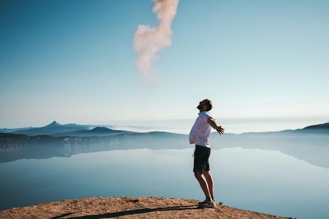 صوره لشخص يقف في قمه جبل