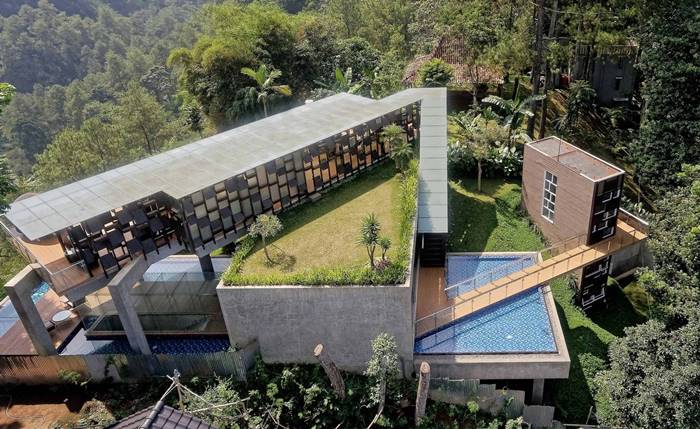 Hanging Villa on a hillside in Indonesia. The architecture of this amazing house enhances the surrounding nature, gently absorbing the features of the landscape, terrain and fauna. Located far from heavy traffic, the villa becomes a convenient place to live and relax a large family.