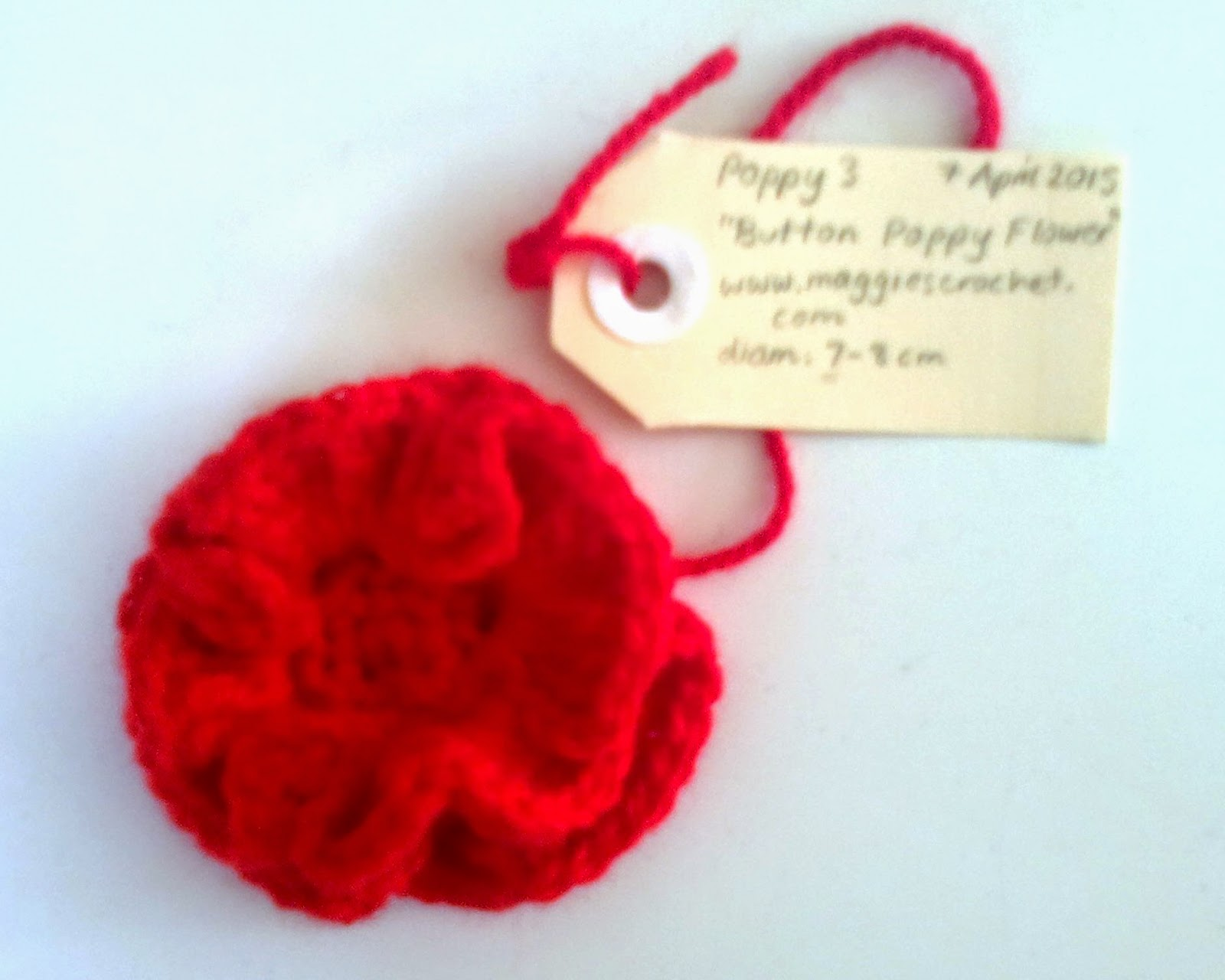 Red crocheted rosette with flat circular centre for a black button to be attached. An identity tag is attached with the loose end.