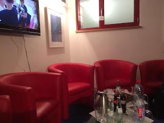 Ein kleiner Raum. In ihm stehen mehrere, rote Sessel im Halbkreis nebeneinander, in der Mitte ein kleiner Tisch mit Getränken