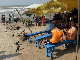 During day time ,tourist taking bath in digha sea and some are enjoying the scene of wave in digha,bengali tourist the mother and son duo are sitting in a stall in beach side