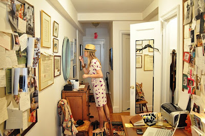 Kate Schelter in straw hat applying makeup in mirror in her NYC apartment - photo by Natalie Joos.