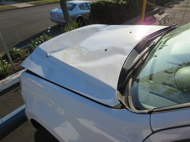 Dramatic hood damage before repairs at Almost Everything Auto Body