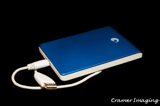 Stock photograph of a blue and white USB external hard drive disk on a black background by Cramer Imaging