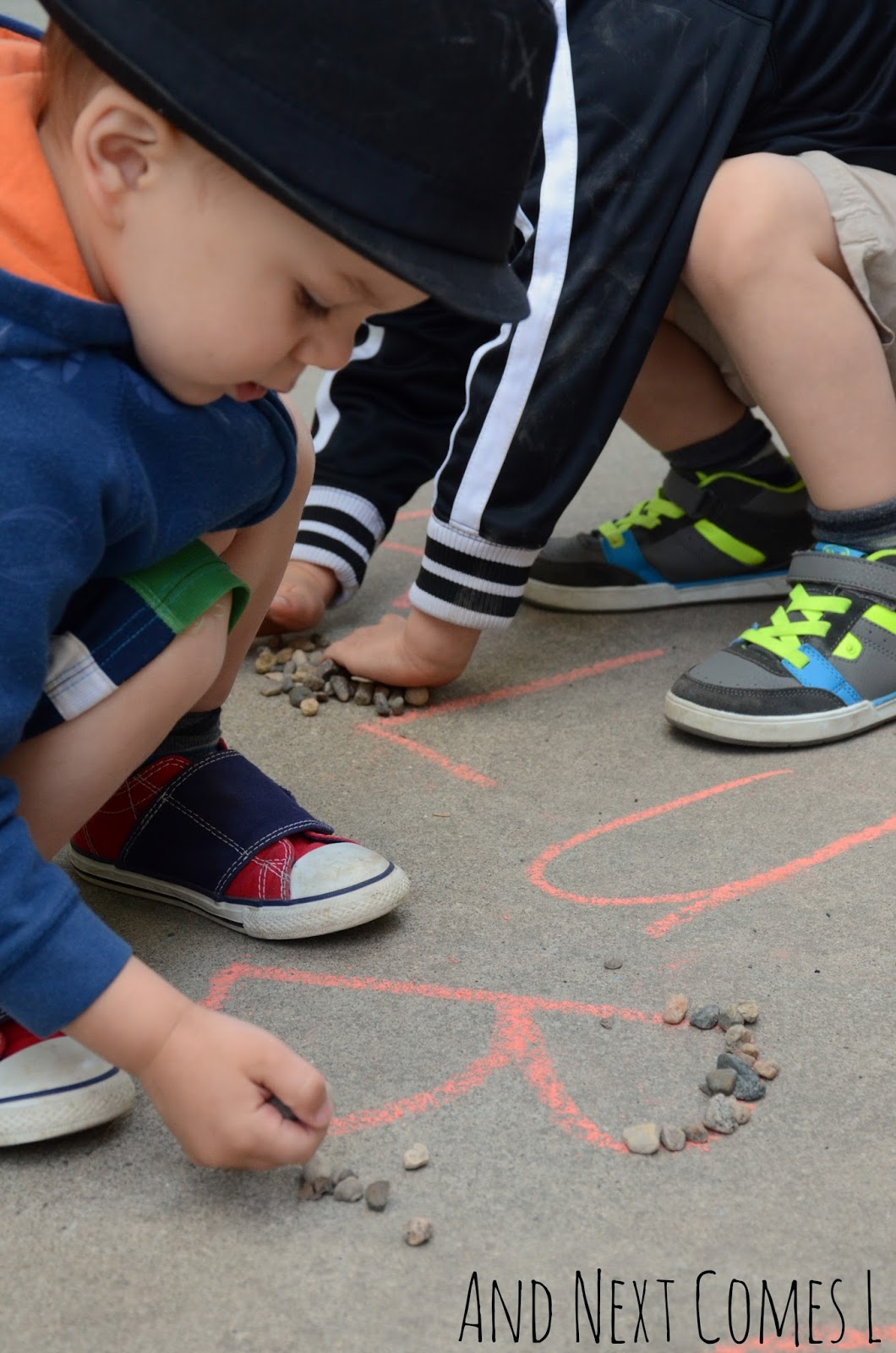 Tracing chalk letters with rocks from And Next Comes L