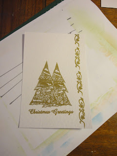 "Two trees, ""Christmas Greetings"" sentiment and line of swirls in gold on white hammered card"