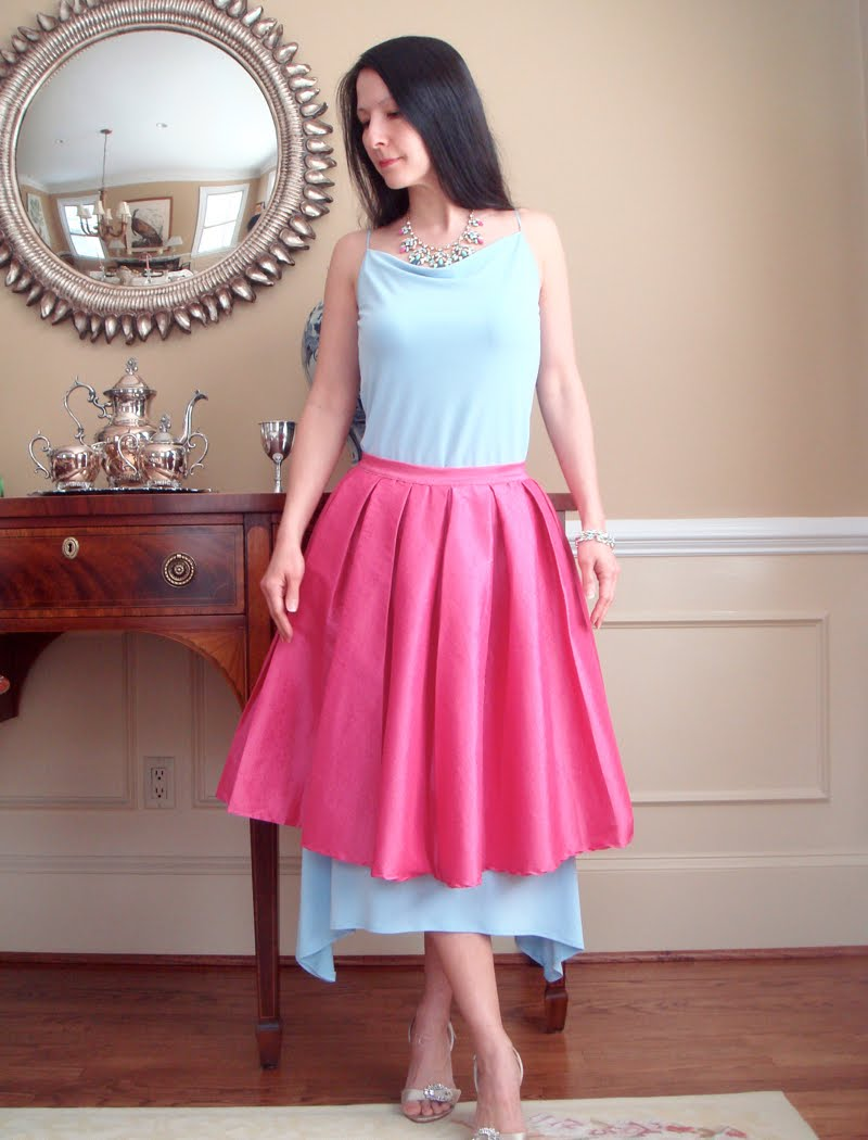 Wearing a blue sleeveless top, blue and pink necklace, blue flowy skirt with a pink full skirt on top and silver sandals.