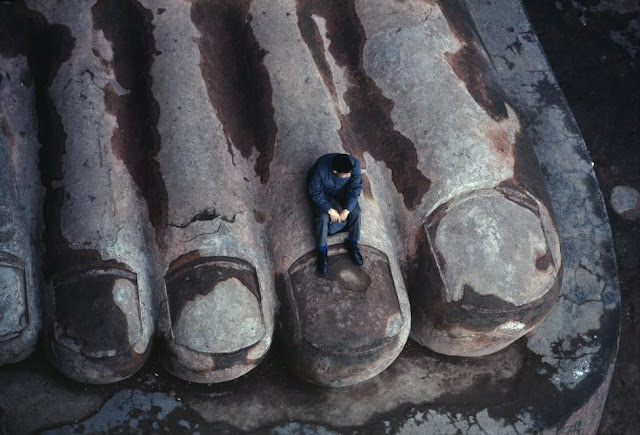 """The Foot of the Leshan Giant Buddha, Sichuan, China, 1980."""" Photographed by Bruno Barbey. Man sitting on the enormous foot of a giant buddah statue, having a moment of reflection, photographed from overhead"""