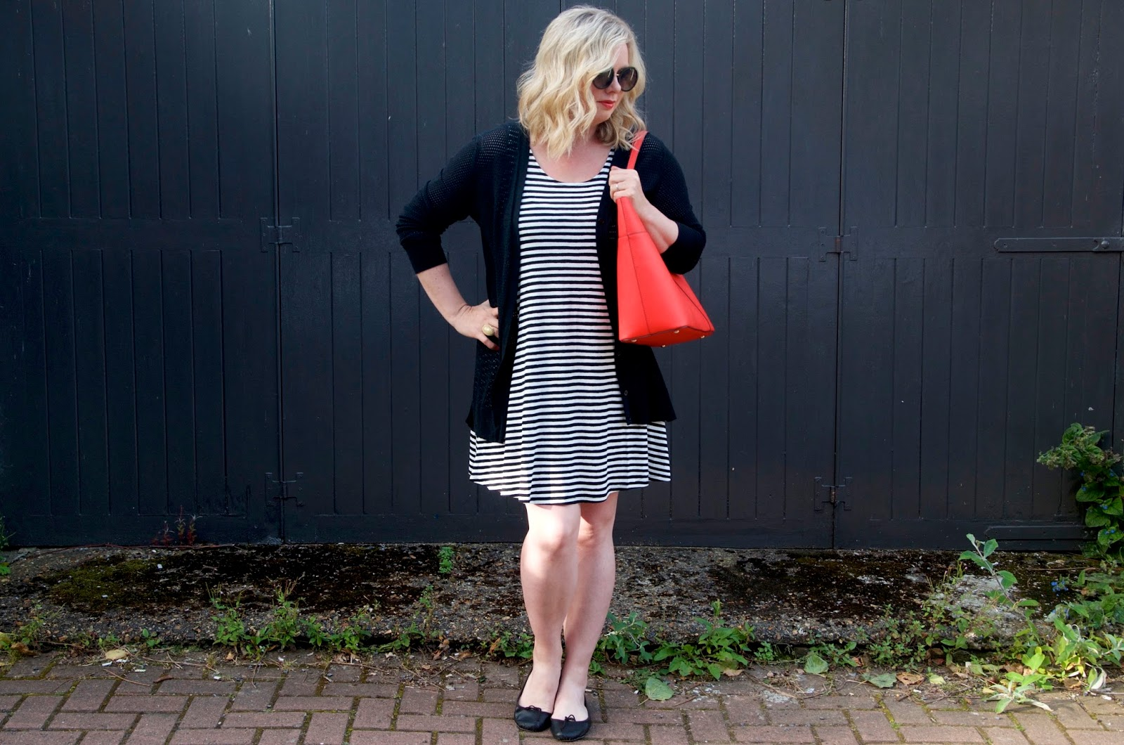 Striped dress, red bag, round sunglasses and black ballet flats