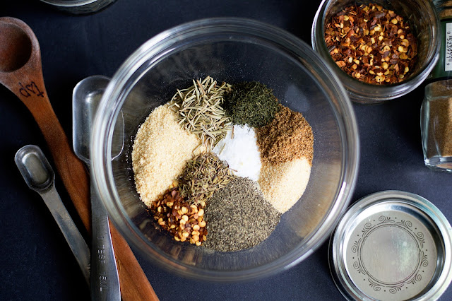 The herbs and spiced used to make the homemade montreal seasoning in a mixing bowl, with measuring spoons and spice pots gathered around it.