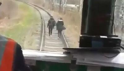 Sepasang kekasih berjalan santai di atas rel