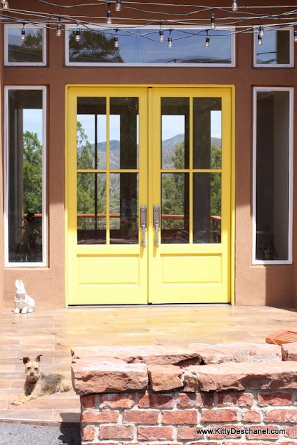 string lights over a yellow door