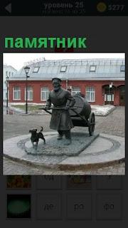 На площади перед зданием на постаменте установлен памятник мужчины, который везет бочку за собой и рядом бежит собачка