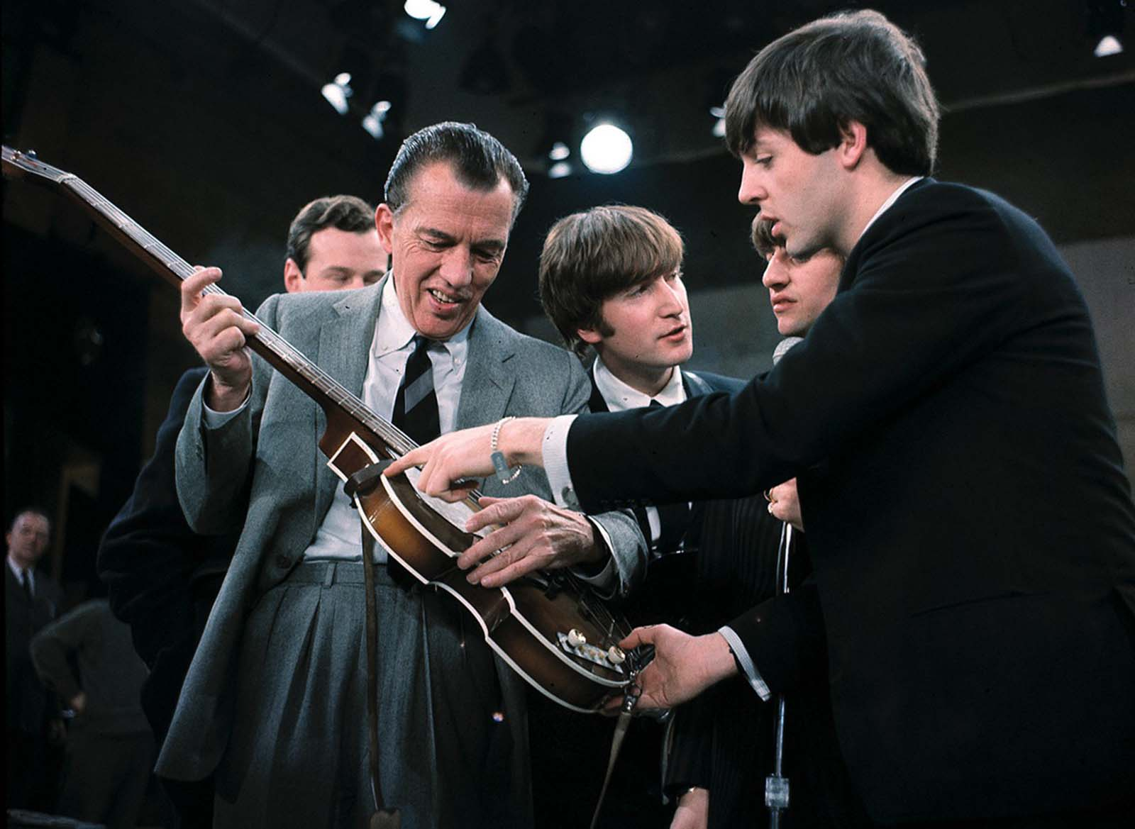 Paul McCartney, right, shows his guitar to Ed Sullivan before the Beatles' live television appearance in New York on February 9, 1964. Behind Sullivan, from left, Beatles manager Brian Epstein, John Lennon, and Ringo Starr.