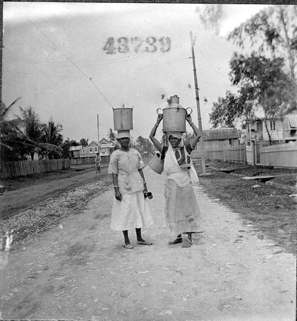 Two women carrying metal jugs of water or milk on their head, standing in street. 1922. Guyana, South America