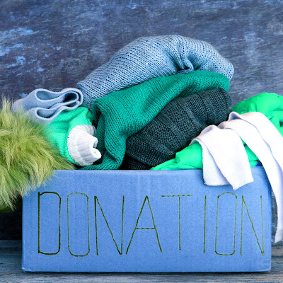 Image of a donation box, overfilled with sweaters and other clothing