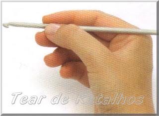 Foto mostrando uma pessoa destra segurando a agulha de crochê com a mão direita no estilo caneta.