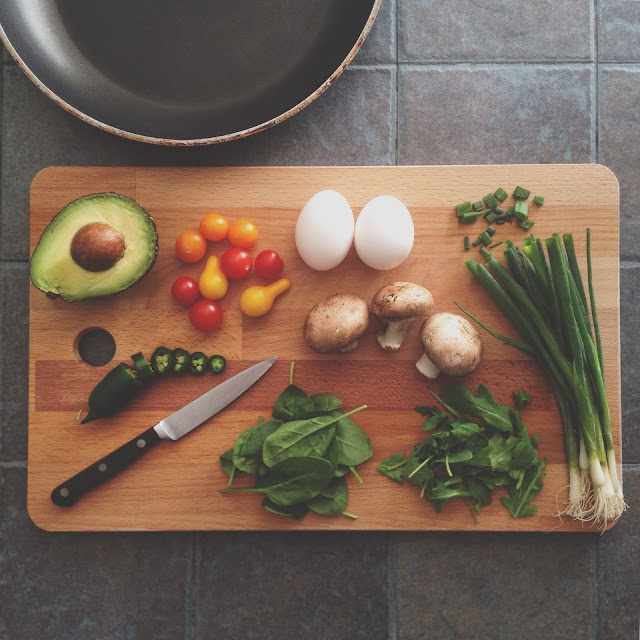 Flatlay of cooking ingredients on a wooden chopping board with a knife, set next to a pan and a tiled background