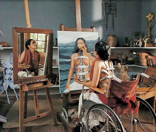 Painting of Frida Kahlo, painting a self-portrait, while also shown in a mirror