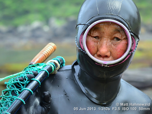 street portrait; headshot; face; South Korea; Facing the World; people; person; closeup; black; East Asia; Jeju Island; Matt Hahnewald; haenyo; free diving; diving grandmother; diving mask; diving suit; seafood; woman free diver; turban shells; abalone; sea urchins; octopus; sea cucumber; tradition; wet; eye contact; eyes; Nikon DSLR D3100; Nikkor AF-S 50mm f/1.8G; portrait
