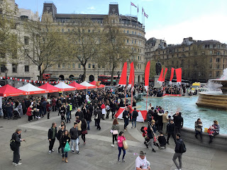 Red and white stall, and fountain with modest crowd in Trafalgar Square