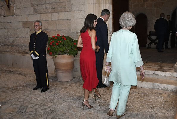 scoop neckline sleeveless fit and flare red dress. Dolce & Gabbana ready-to-wear collection, gold clutch. Queen Sofia