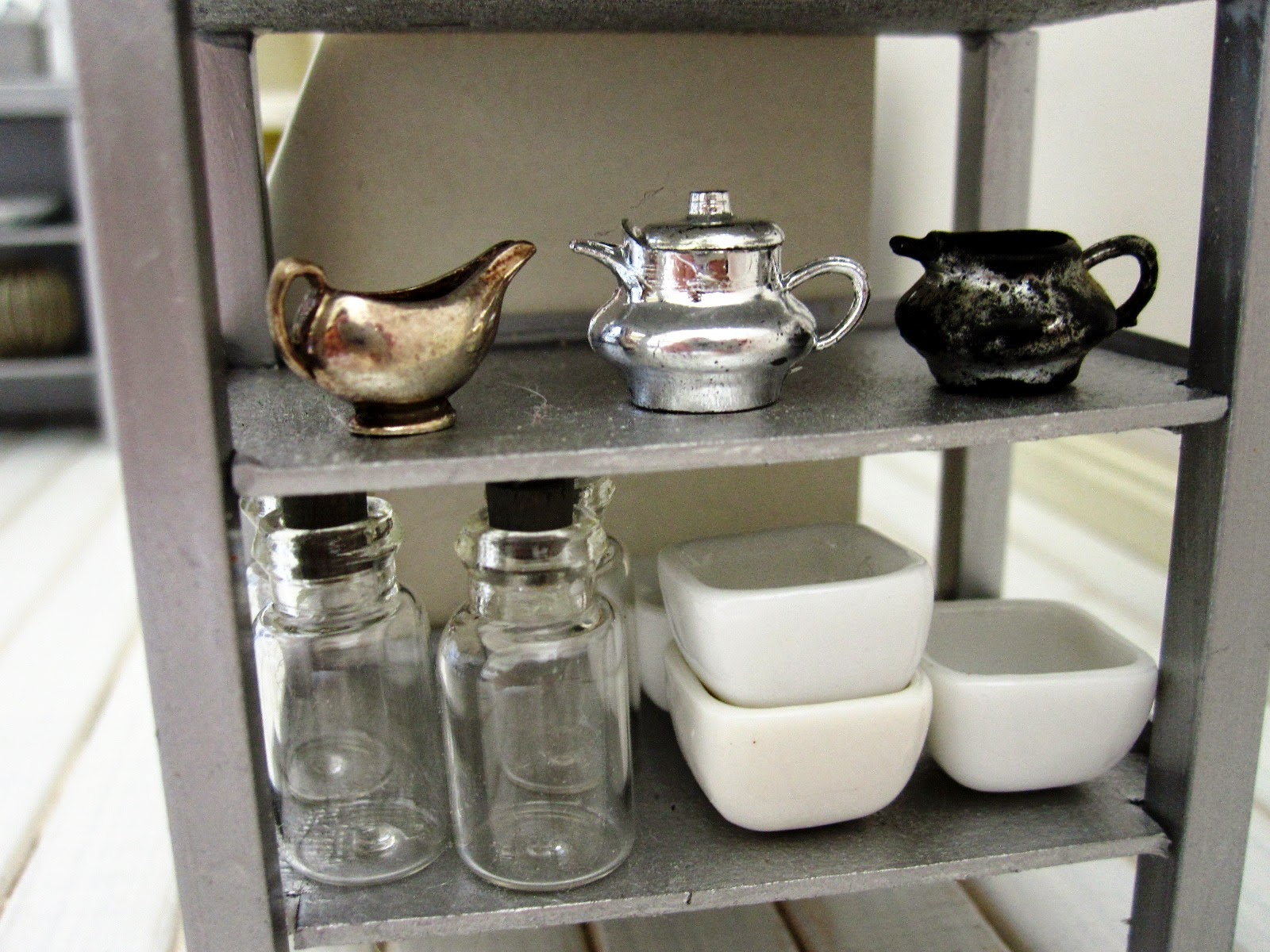 Close up of  a modern dolls' house miniature display of homeware. On the top shelf are three silver vintage jugs, and below are several glass bottles and white bowls.