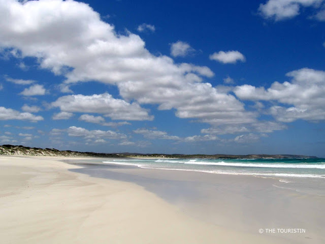 Secluded and wide white sand beach with blue-green water under a blue sky with big fluffy clouds.