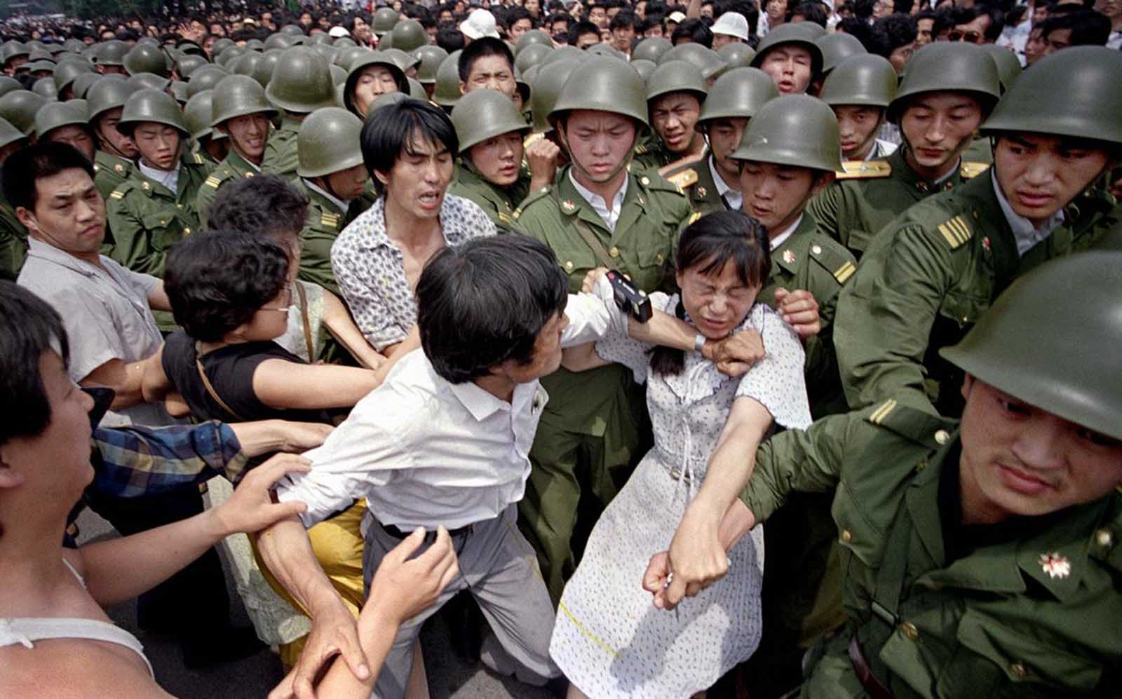 A young woman is caught between civilians and Chinese soldiers, who were trying to remove her from an assembly near the Great Hall of the People in Beijing, on June 3, 1989.