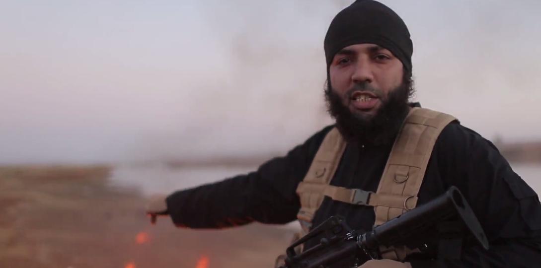Un djihadiste montre l'endroit où les deux soldats ont été brûlés, dans la province d'Alep, en Syrie.